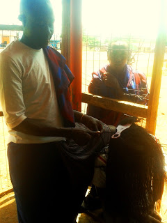 Maasai moran plaits a woman's hair into African braids by rolling them to twist on his thigh braids as a fellow moran medicine man watches on