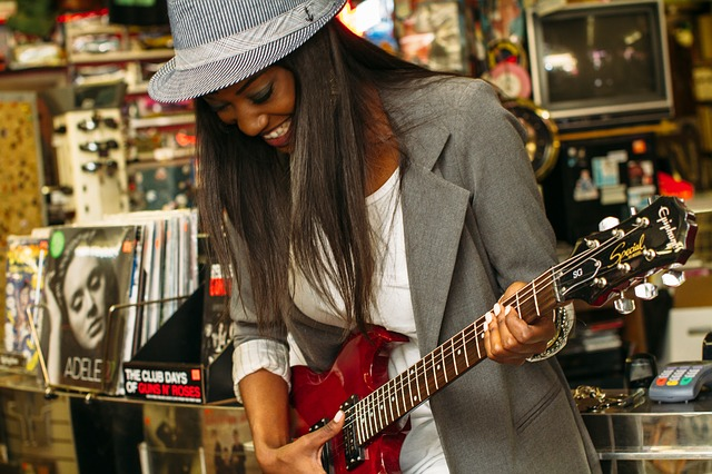 A young, chic African woman smiles as she tries out a gitar in a music store personifies the future of Kenyan Music in the 21st century as modern, young and a collage of individual styles