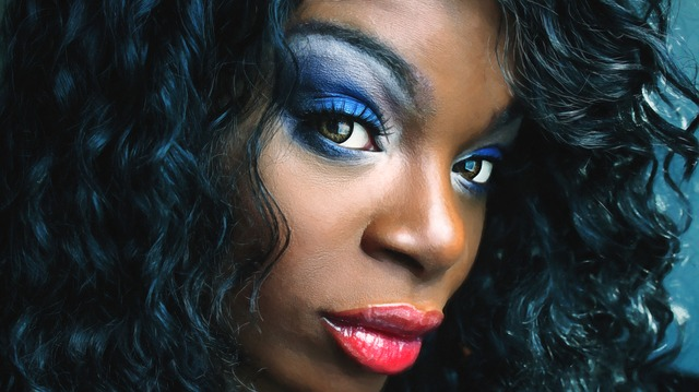 African woman with bold blue makeup proving that it's how you wear the makeup that give you confidence, not the inverse.