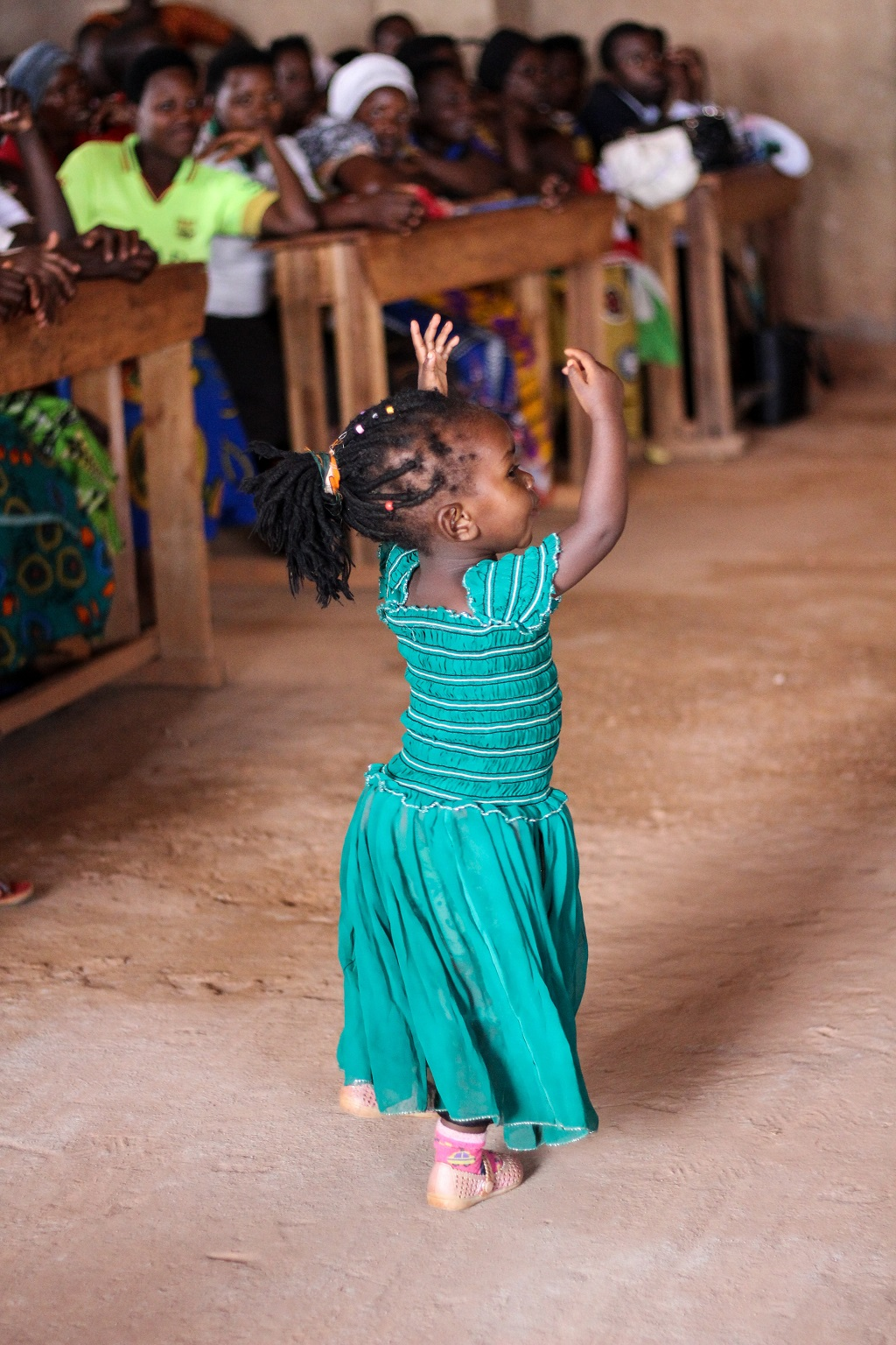 african girl, barely five in age, in green dress dances in church as congregation wathces on