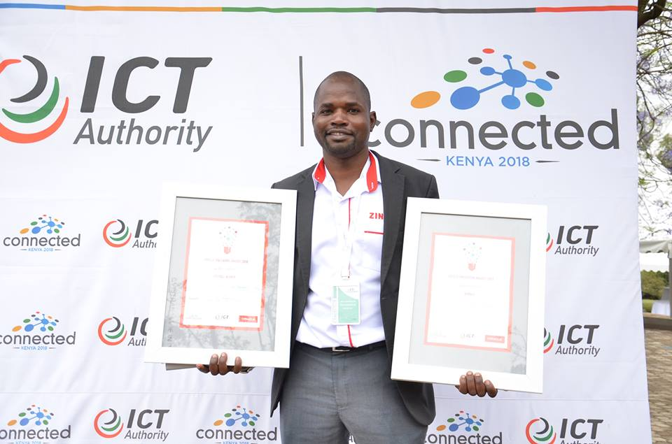 enyan award winning entrepreneur Gervase Jeneri Wakoli holds up to awards during the Connected Kenya -2018 conference